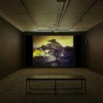 Derek Jarman, installation view of The Last of England exhibition at Void Gallery, 2019, film still from The Last of England film, featuring a young woman dancing in a wedding dress with a yellow sky behind
