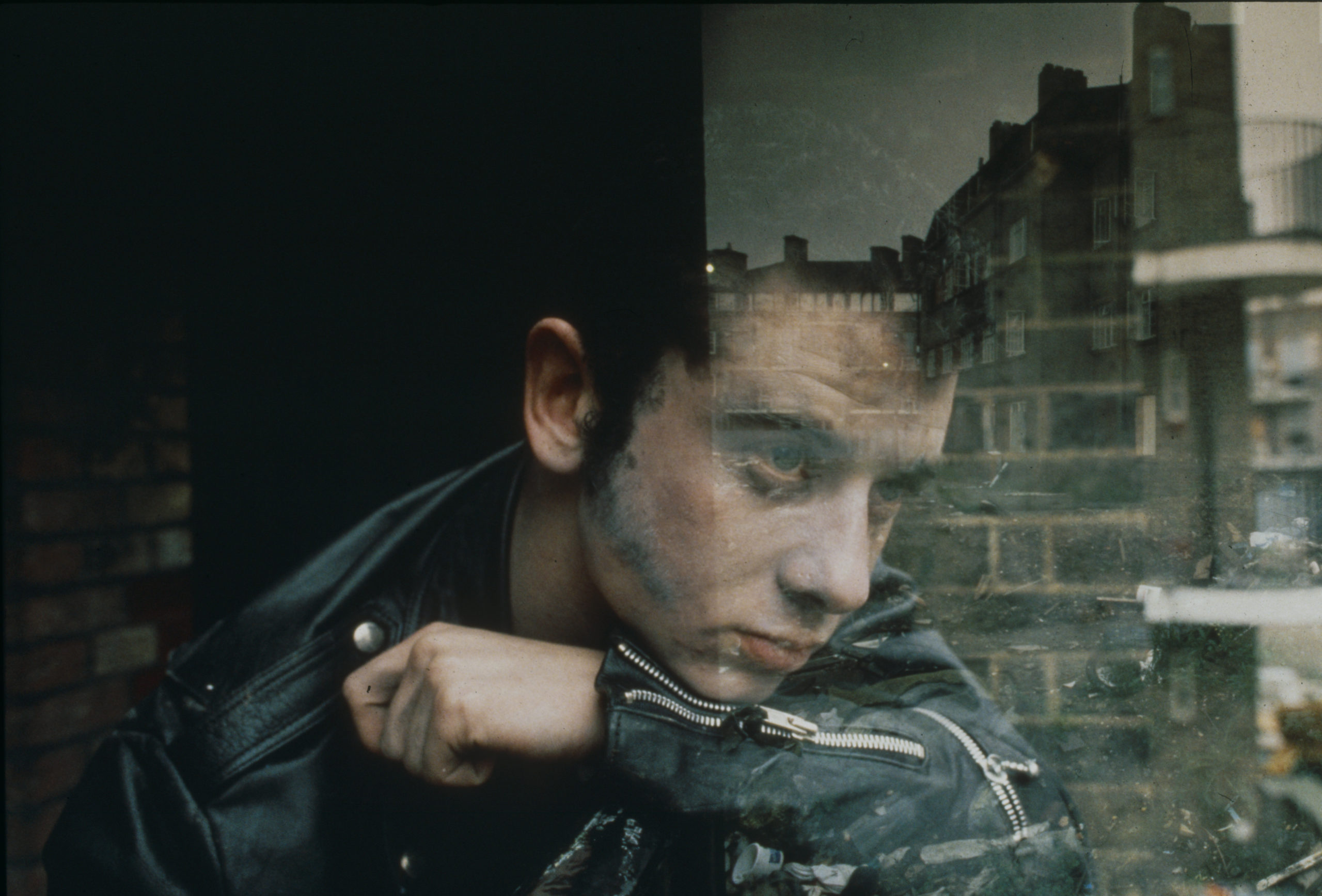 Film still from The Last of England film by artist Derek Jarman, image depicts man looking out a window with the reflection of a red brick building displayed to the right of the image