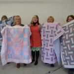 A Stitch In Time participant group photo with the quilts they made during the workshop