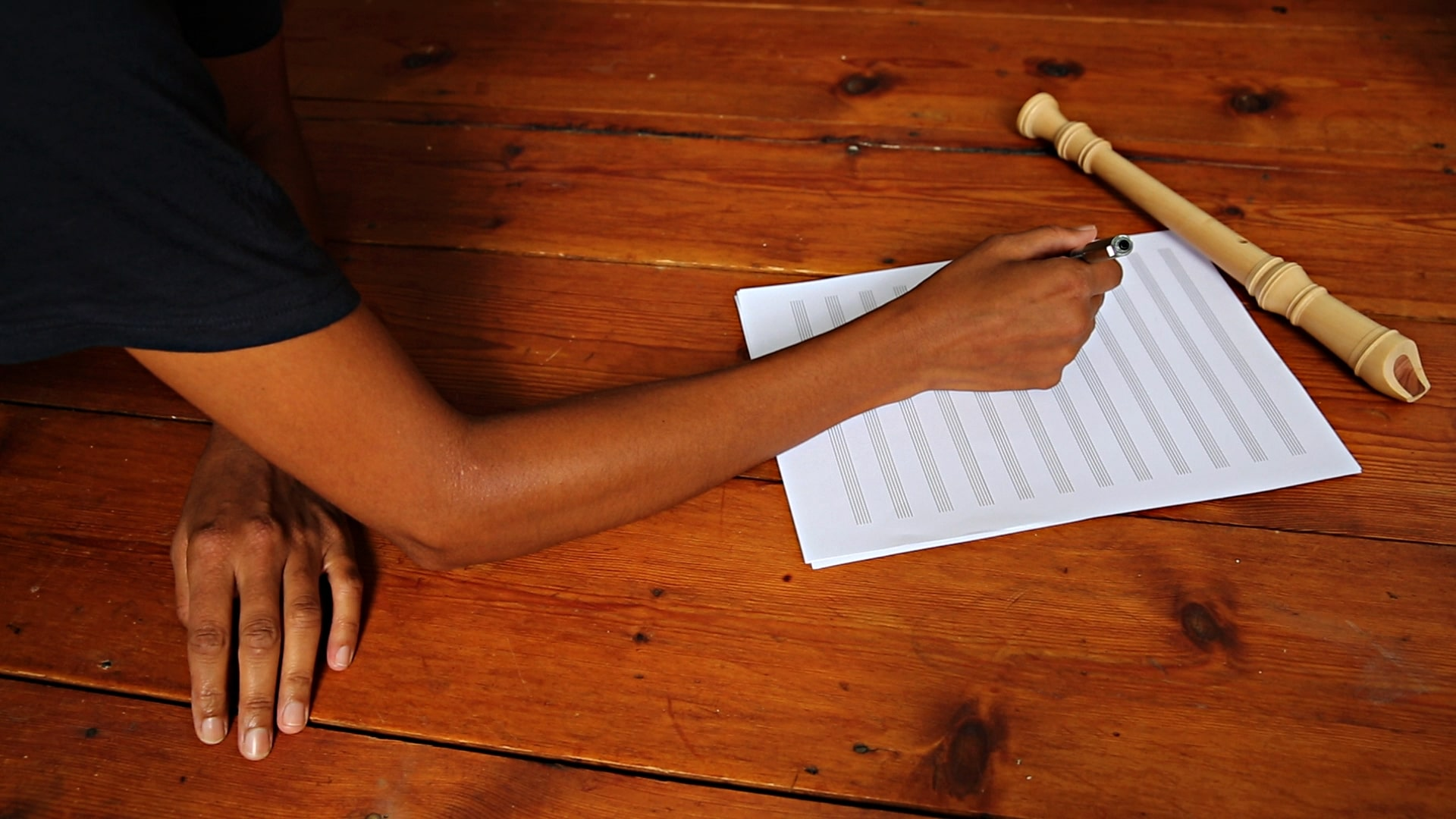 The Long Note by Helen Cammock, promotional image, woman's arm extends as she writes musical notes on a music sheet with a recorder sitting off centre, a warm wooden floor underneath her
