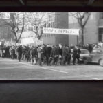 Installation view of The Long Note by Helen Cammock, at Void Gallery, film still, marchers for People's Democracy march